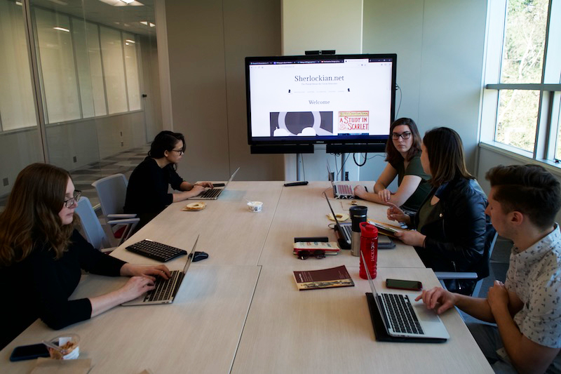 Group of people at a conference table working on laptops while a project is displayed on a tv behind them