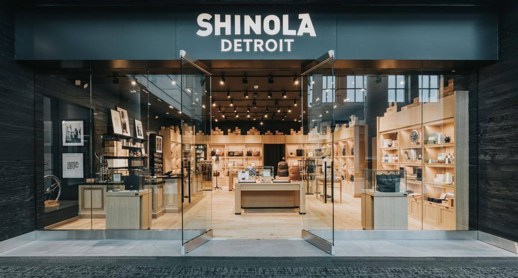 Storefront of Shinola, a luxury goods store. The front walls are glass and trimmed with dark black wood and show the inside which has light wooden fixtures and bright lighting.