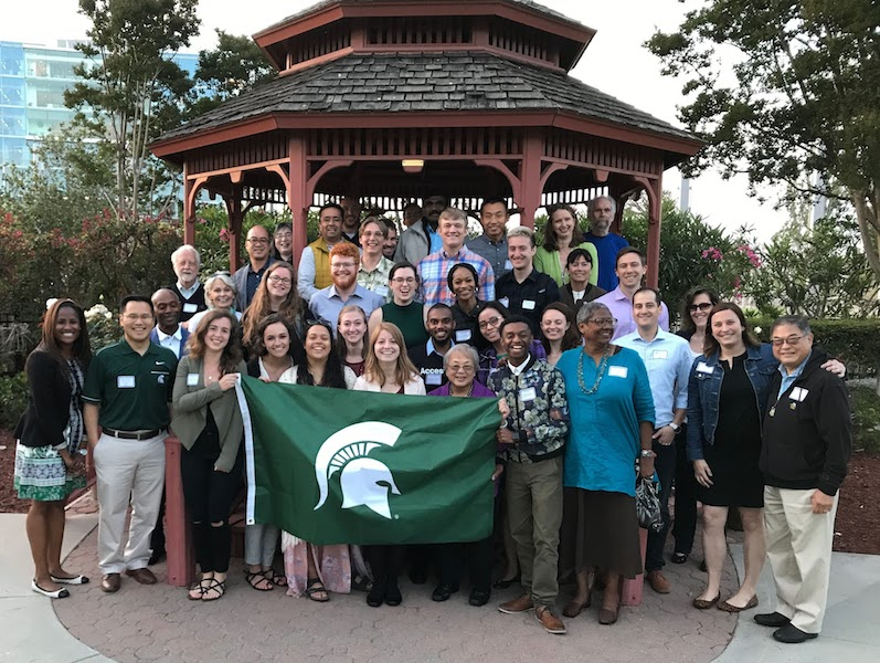 a group of students and faculty holding the MSU flag