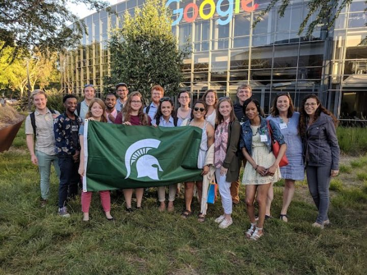 large group in front of google building holding MSU flag