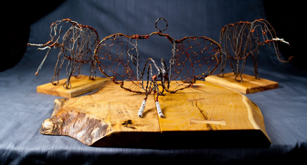 art of elephants made out of wire and beads standing on polished wood