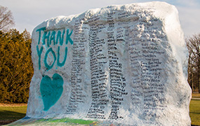 """msu rock painted white with teal """"thank you"""" and heart and black signatures"""