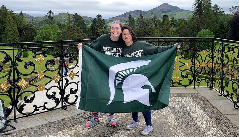 two girls wearing MSU sweatshirts holding an MSU flag