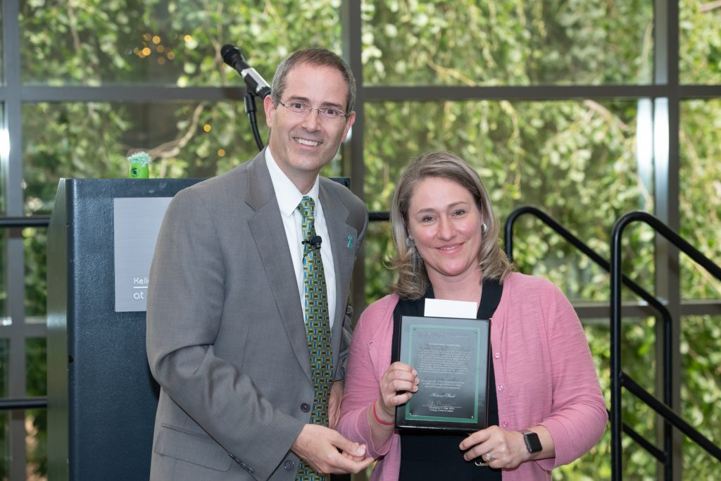 a man a man in a grey suit coat with a white shirt and green neck tie and a women with blonde hair in a pink button down sweater and black shirt holding a award