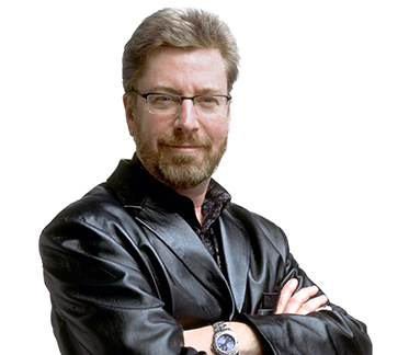 a man with facial hair wearing glasses and a leather jacket