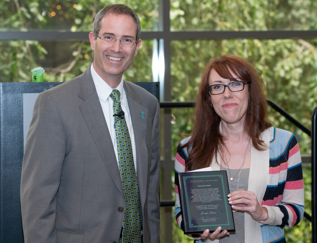 a man in a grey suit coat with a white shirt and green neck tie and a women with long hair and glasses wearing a colorful cardigan and grey shirt holding an award