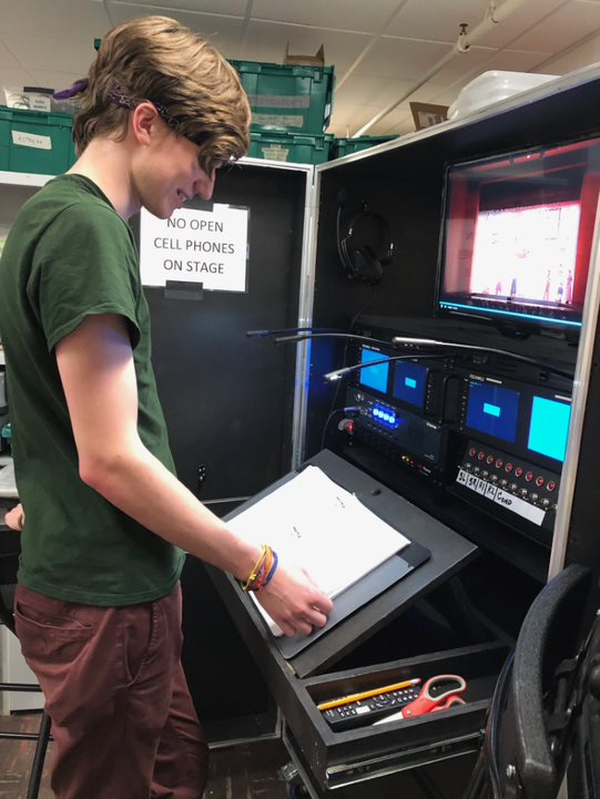 A student simulating calling a show using a prompt book and video