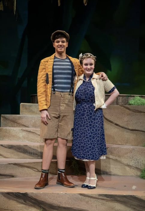A man (left) and a woman (right) standing on a stage. The man is wearing a yellow jacket, striped shirt, cargo shorts, and a hat. The woman is wearing a blue ankle-length dress and a tan cardigan.