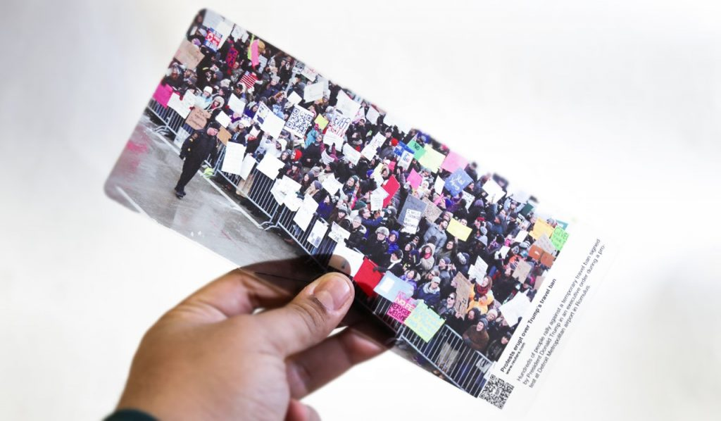 A hand holding a picture of a protest contained behind a fence