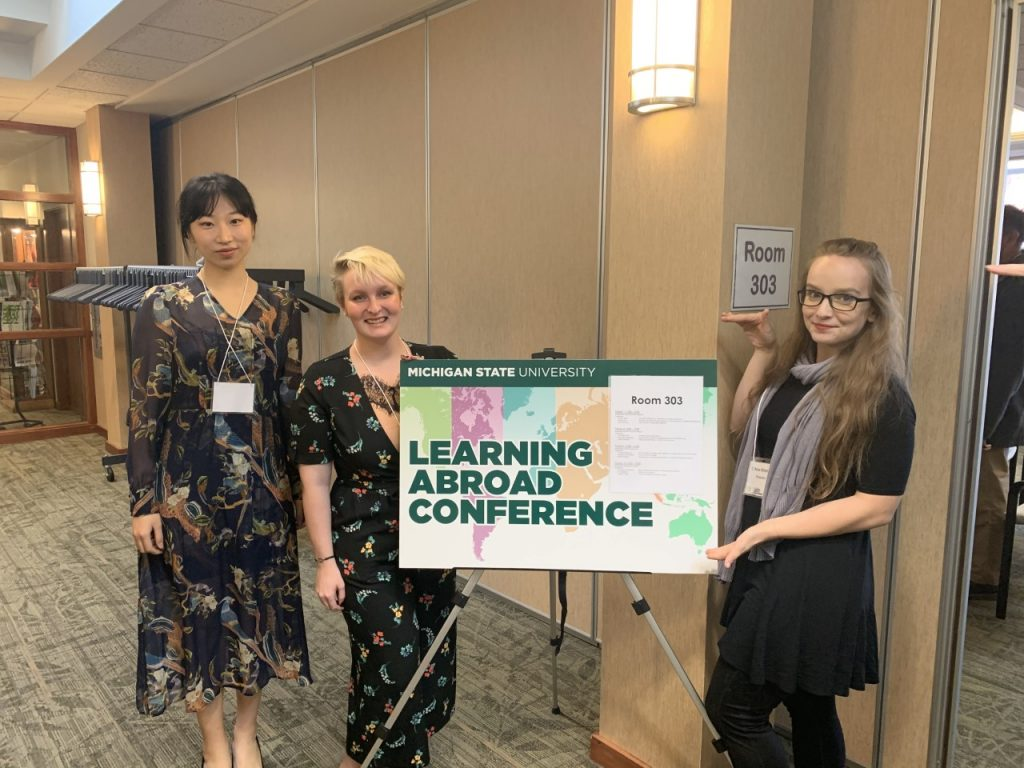 three people standing in front of a learning abroad conference sign