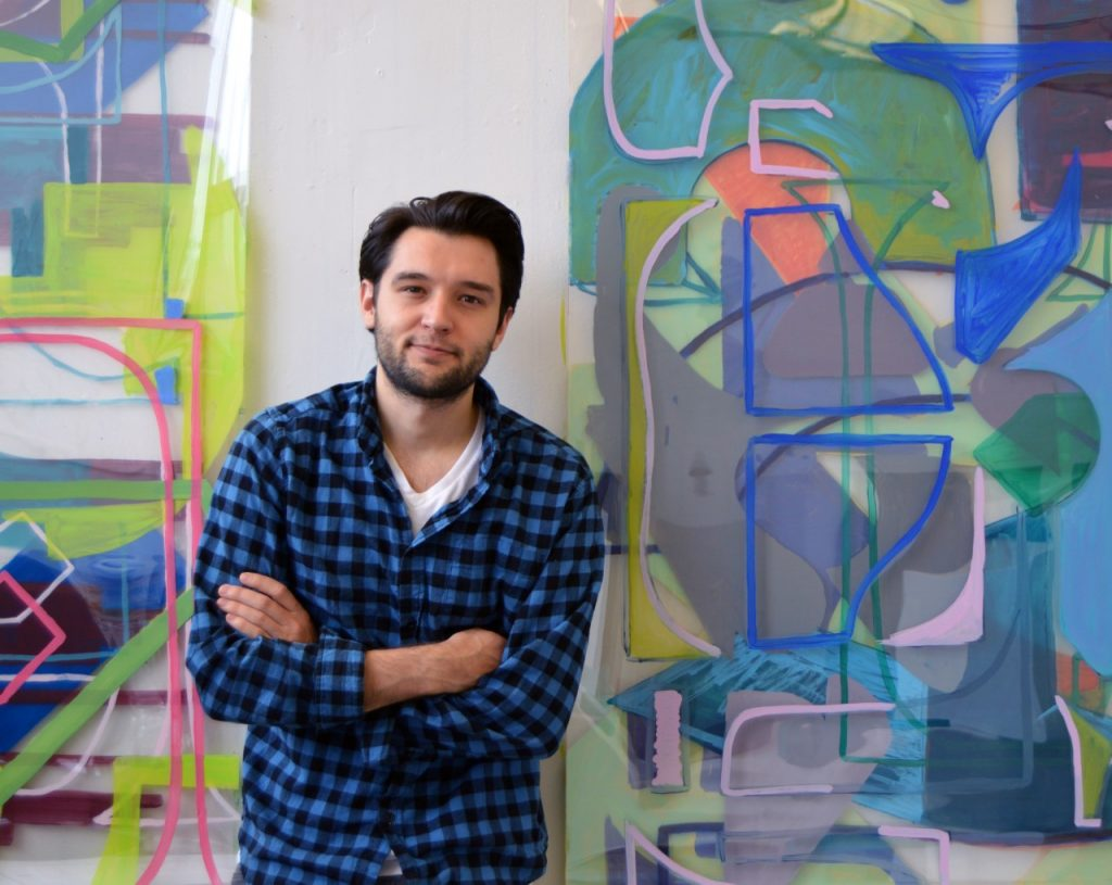 Man with black hair standing in front of a colorful art exhibit. He is wearing a blue and black checkered shirt.