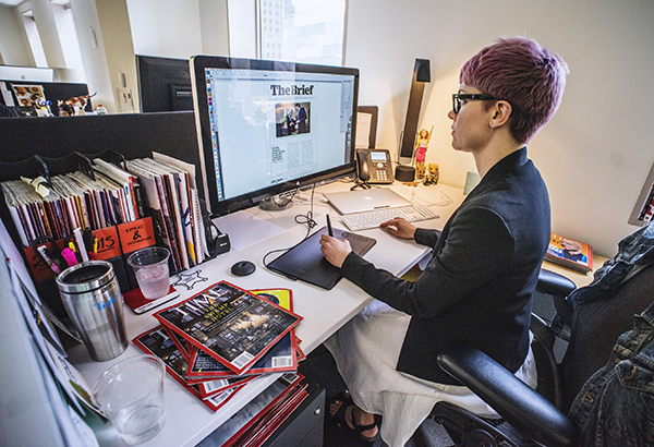 woman with short pink hair sitting at desk working on time magazine spread on the computer