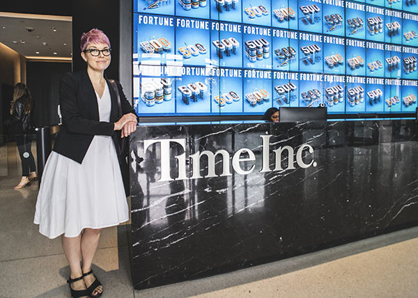 woman with short pink hair standing in front of time inc sign