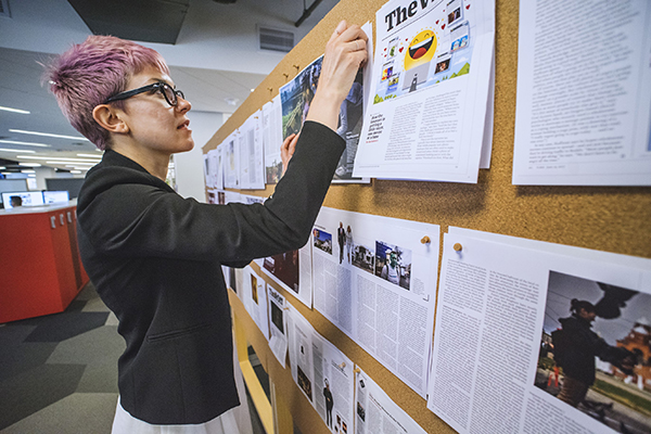 woman with short pink hair pinning magazine layout spreads to bulletin board wall