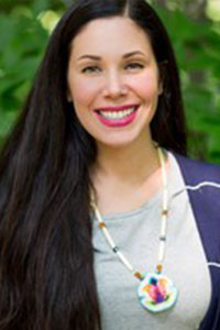 head shot of a woman with black hair, gray t-shirt, white necklace, and striped dark blue cardigan