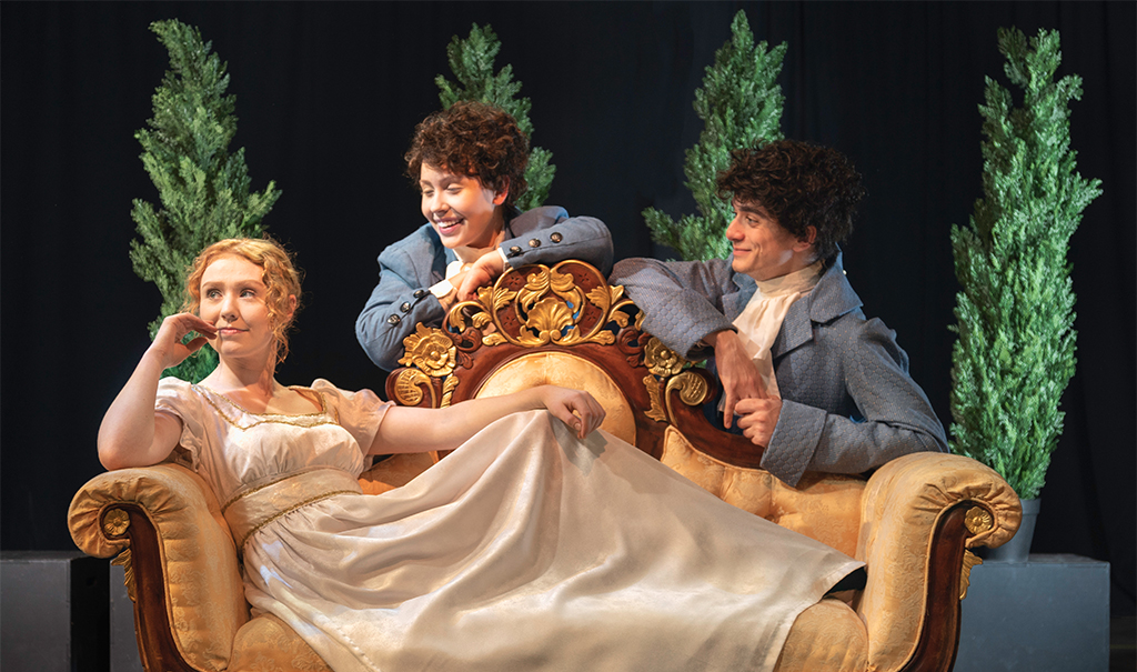 woman wearing a long white dress who's sitting on a couch and looking off into the distance while two men are sitting behind her and smiling at her