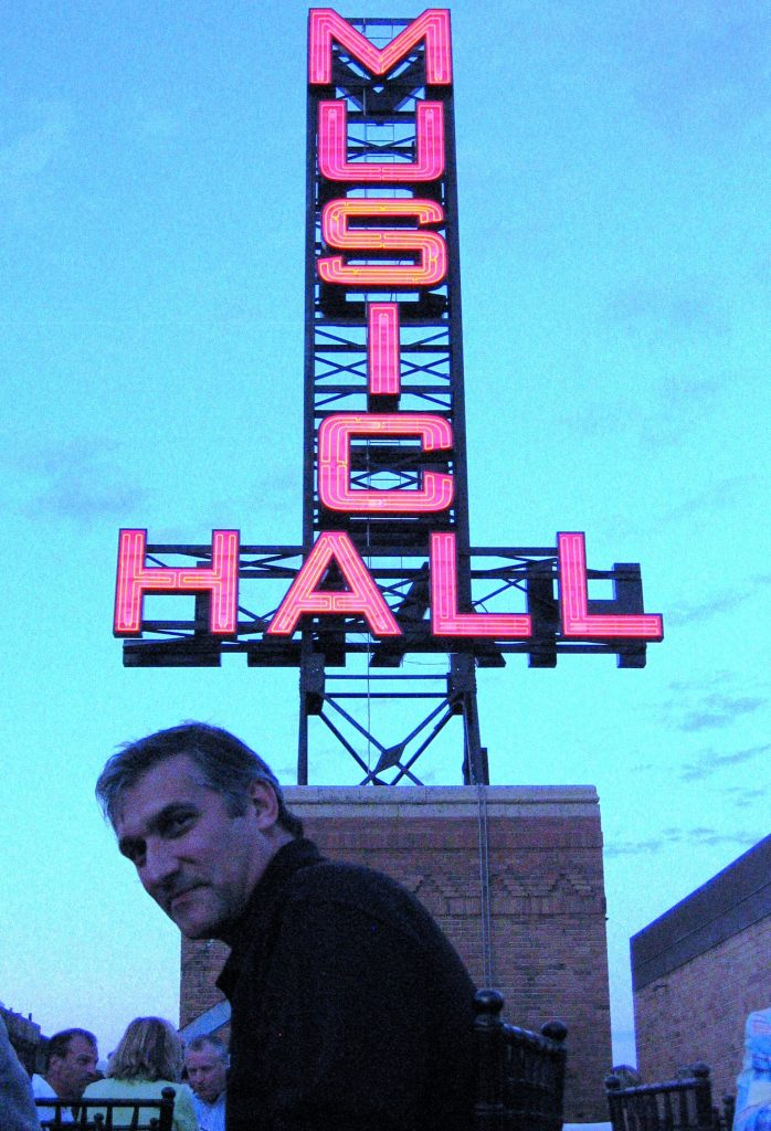 man wearing a black shirt sitting in front of large neon sign that says music hall
