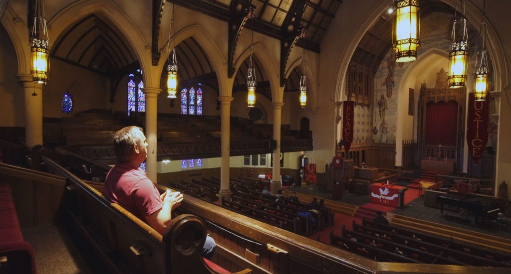 Man wearing red sitting in a church praying