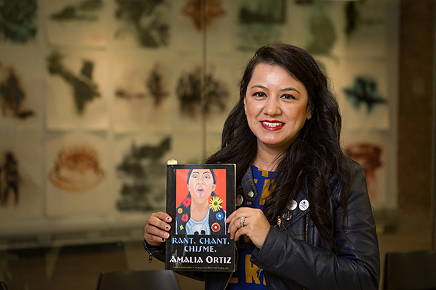 Photo of a woman with dark hair smiling at the camera holding her book