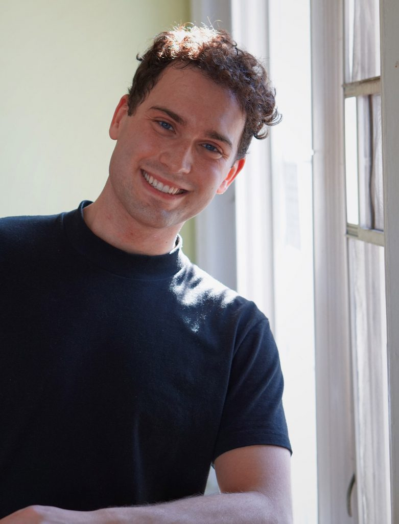Man in a navy blue t shirt leaning on a window smiling at the camera