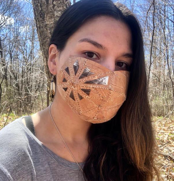 a woman with long dark hair wearing a grey shirt and a homemade mask