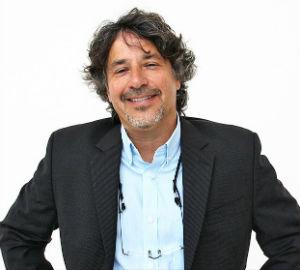 man wearing a blue shirt and black jacket smiling at the camera