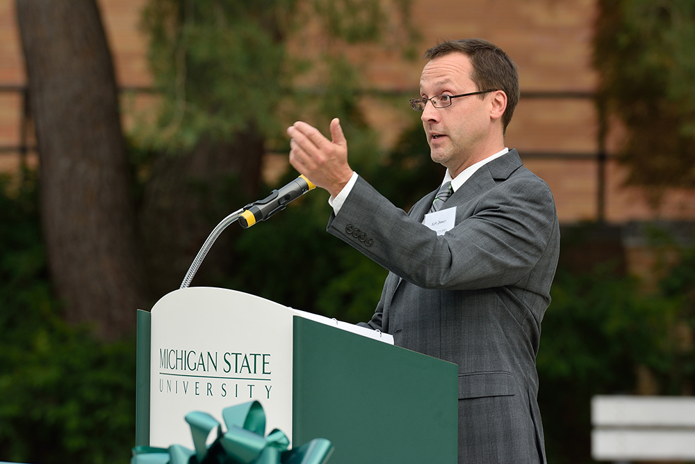 man wearing a gray suit and glasses with his arm up speaking into a microphone at a green podium