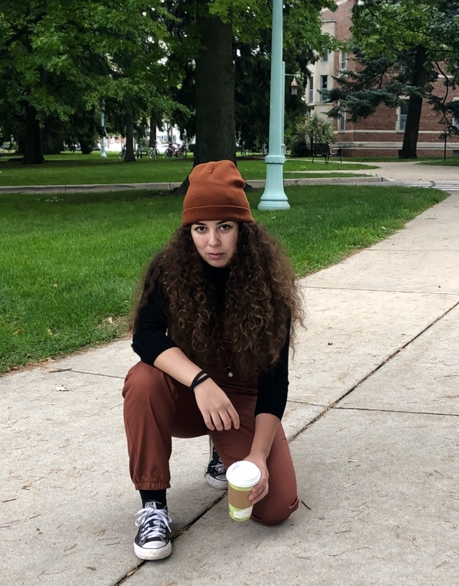 Woman in a black shirt and an orange hat kneeling in front of the camera