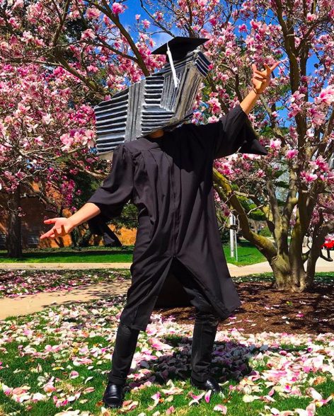 Man wearing a black graduation gown with a paper mâché version of the Broad Art Museum on his head