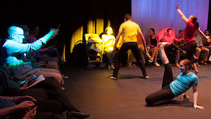 Photo of a stage with several people doing multiple different kinds of dances.