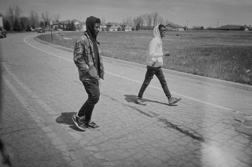 black and white image of two men walking down a street