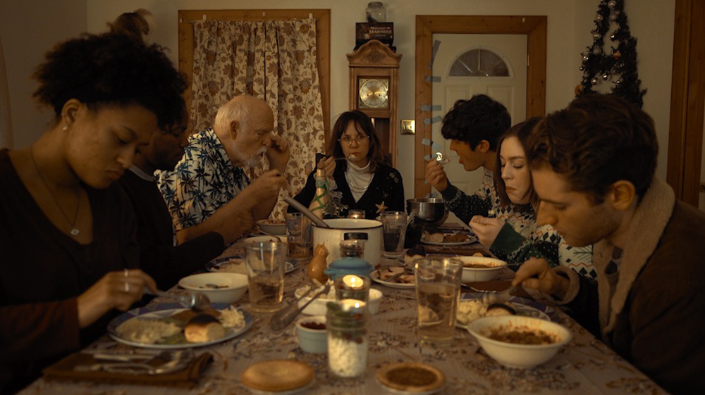seven people sitting at a table eating food