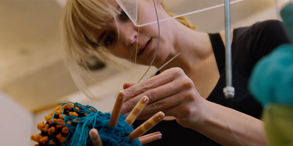 a woman with blonde hair pulled back working on an art piece