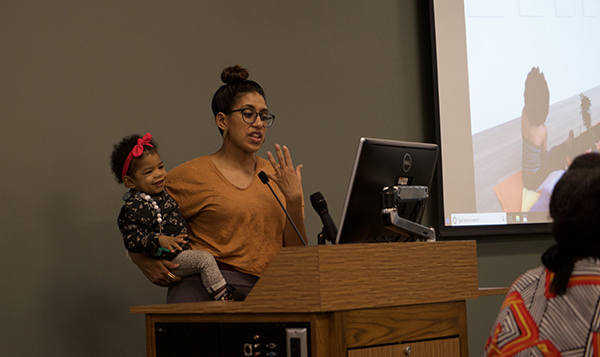 woman in glasses lecturing behind a podium while holding a child
