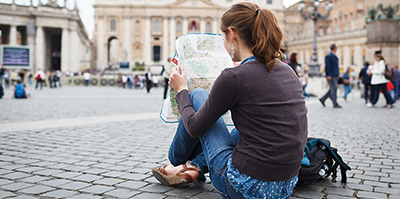 a woman with brown hair in a ponytail in a long sleeve and jeans reading a map