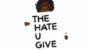 """Photo of a girl holding a sign that says """"The Hate U Give"""""""