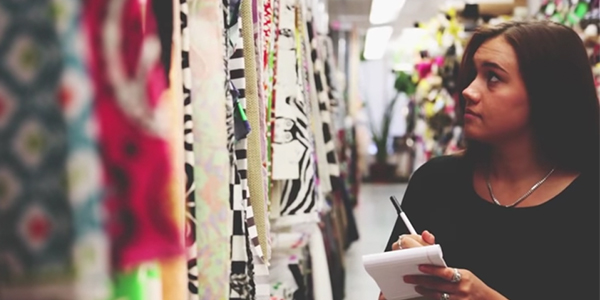 woman walking through textile store with notepad and pencil
