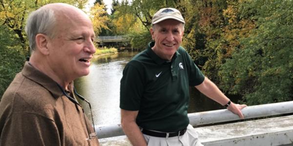 two older men taking a walk around campus