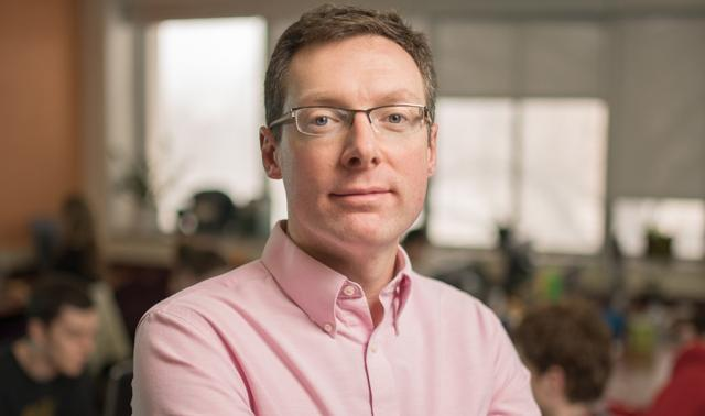 a man with short hair wearing glasses and a pink shirt