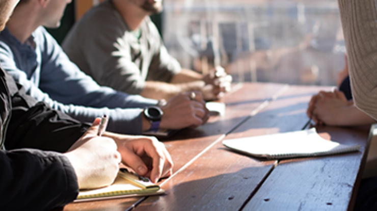 People taking notes together at a wooden table