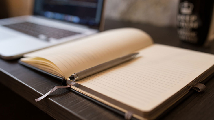 A open note book and computer on desk
