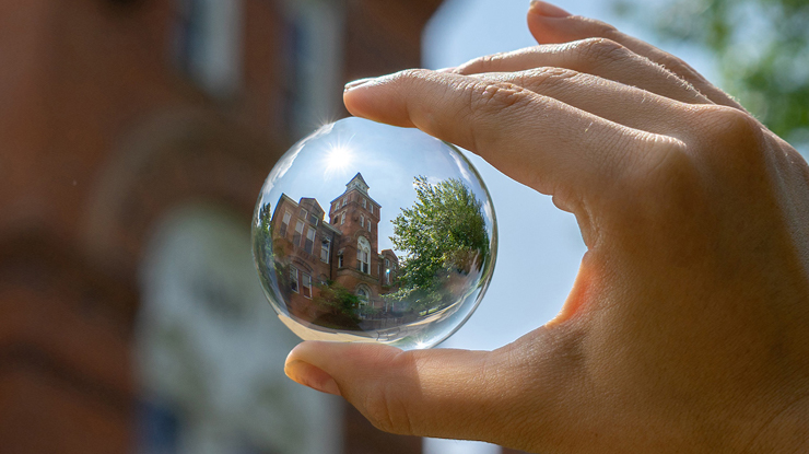 Hand holding a glass ball reflecting Linton hall on the inside
