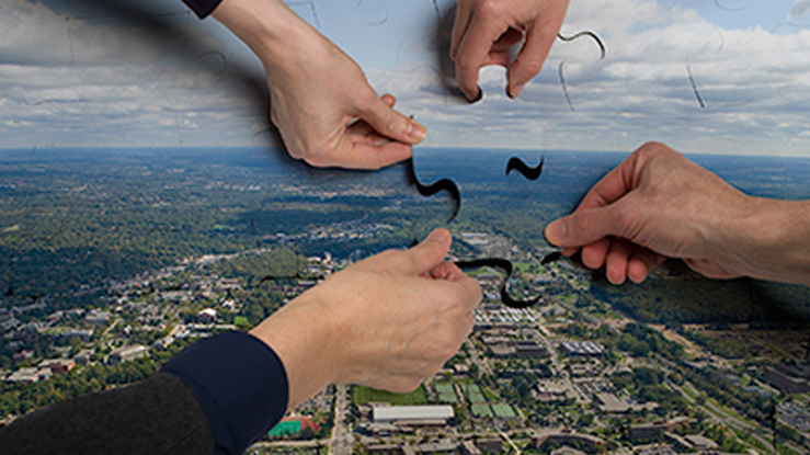 Hands putting together a puzzle of an aerial view of MSU's campus