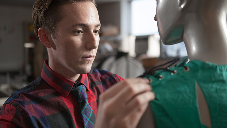 a person with a plaid shirt and colorful tie working on a dress on a mannequin