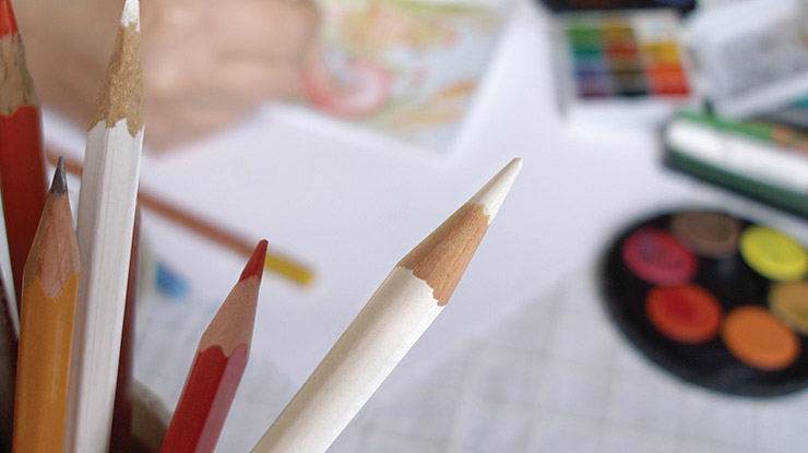 closeup of colored pencils with an art desk in the background