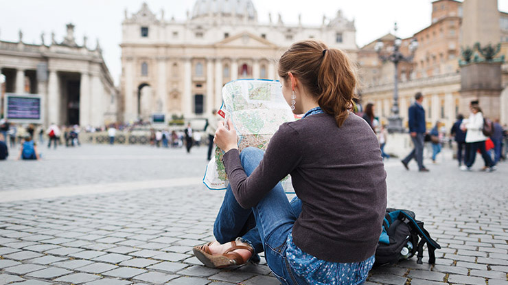 a woman with brown hair up in a ponytail reading a map