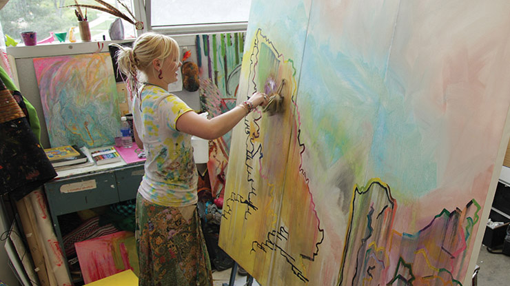 a woman with blonde hair painting a picture