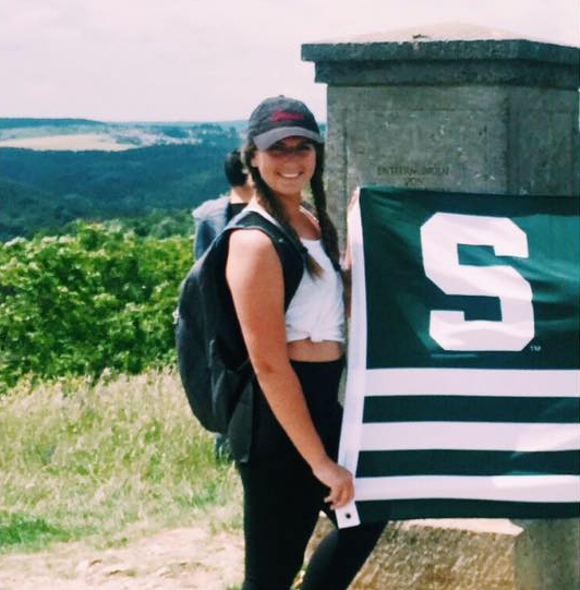photo of a young woman smiling and holding a spartan flag outdoors. she is wearing a gray cap, white top, black leggings, and a backpack