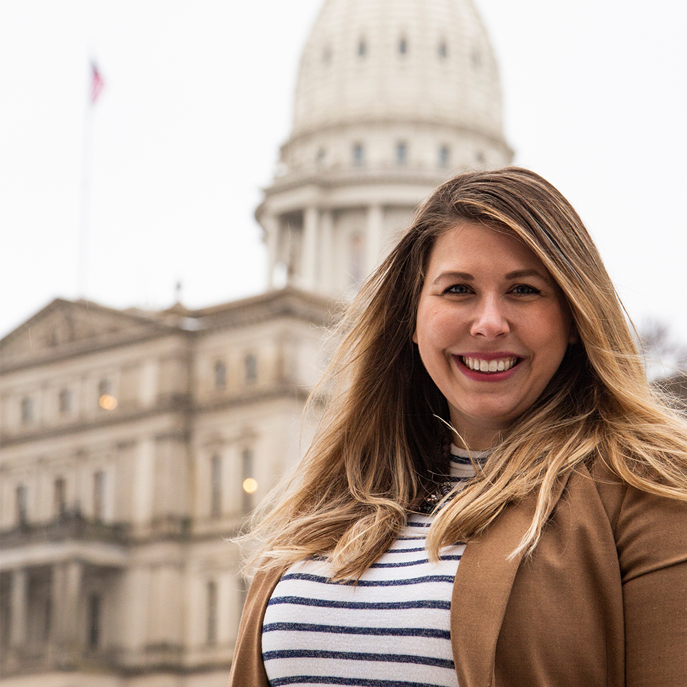 a woman with long blonde hair wearing a striped shirt with a brown blazer standing in front of the Michigan State Capitol