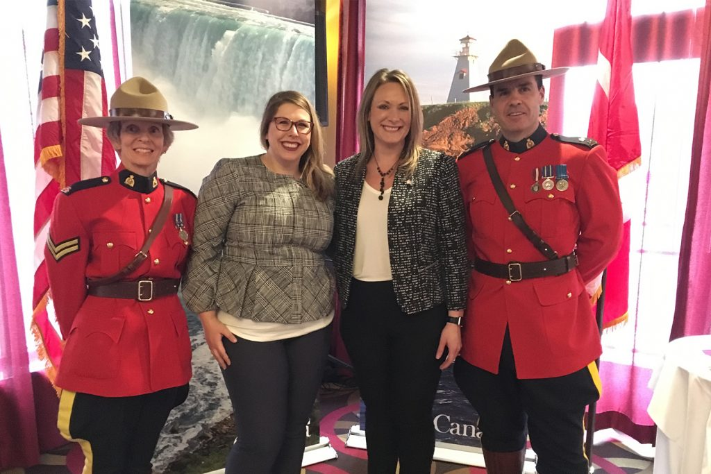 four people standing in line: from left to right; Canadian Mountie, Katelyn Wilcox(alum), Lindsay Kirchinger (Katelyn's boss), Canadian Mountie